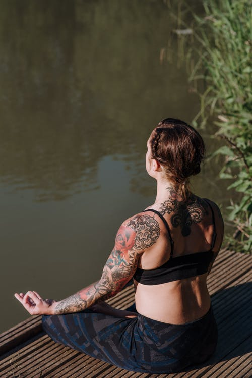 Back view of anonymous female in sports clothes sitting in Lotus pose while practicing yoga on pier against river