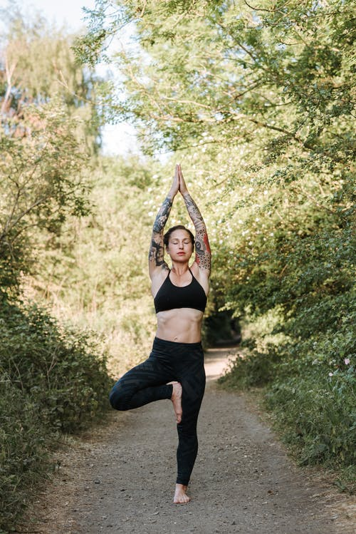 Concentrated woman performing Tree pose on pathway in summer
