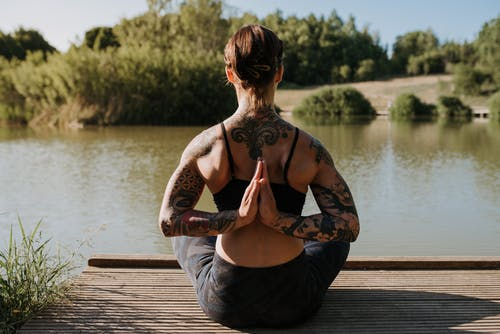 Back view of anonymous tattooed female in sportswear sitting in Reverse Prayer pose on wooden dock against river