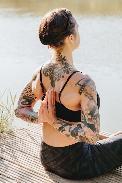 Anonymous tattooed woman meditating in Reverse Prayer pose