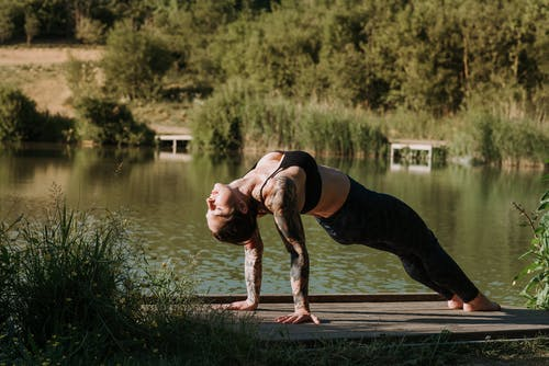 Side view of young female in sportswear with closed eyes performing Purvottanasana pose while practicing yoga on dock against pond