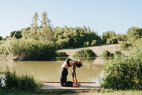 Side view of young barefoot tattooed lady showing Ustrasana pose while practicing yoga on pier near river and bushes
