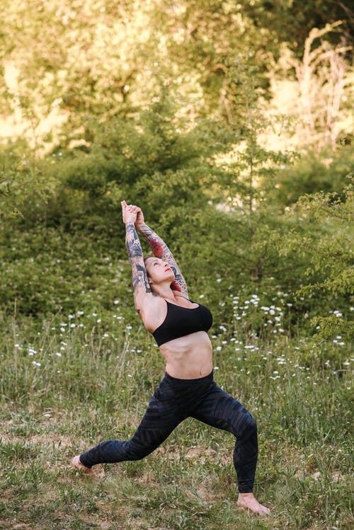 Attentive tattooed woman showing Warrior pose on grass