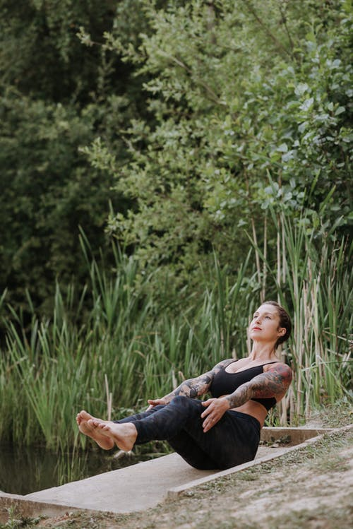 Young attentive tattooed female in sportswear sitting in Navasana pose while practicing yoga on pier and looking up