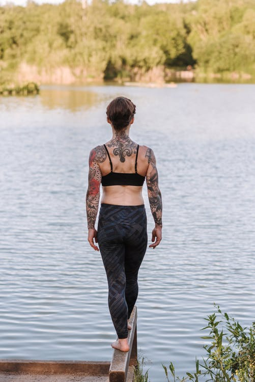 Back view of anonymous barefoot female in sportswear standing on wooden dock against lake and trees