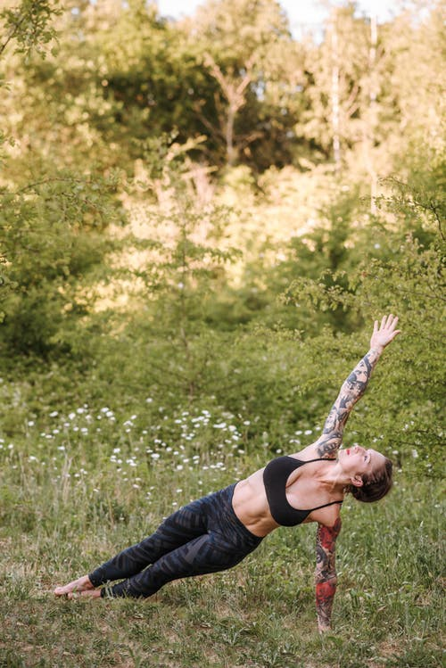 Tattooed woman performing Side Plank pose on meadow