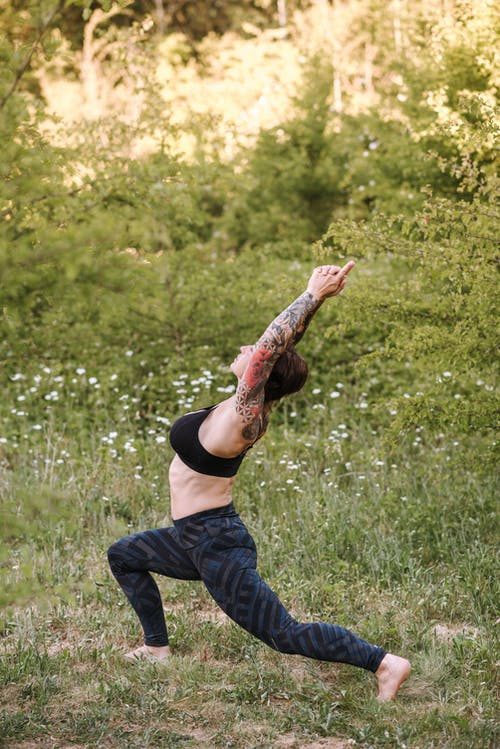 Side view of unrecognizable tattooed female in sports clothes demonstrating Virabhadrasana pose while practicing yoga on lawn