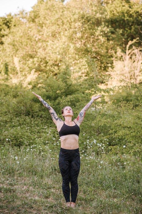 Tattooed woman standing in Urdhva Hastasana pose on meadow