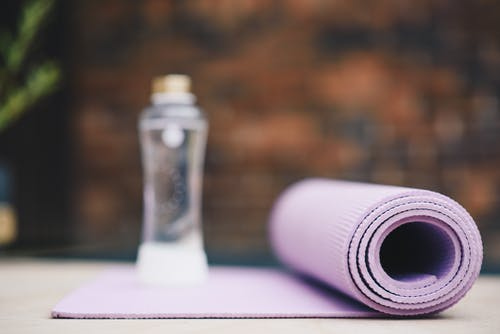 Roll of violet yoga mat with transparent plastic bottle of water on blurred background