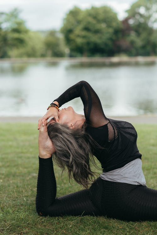 Side view of young mindful female sitting in Hanumanasana pose with raised leg and closed eyes while practicing yoga against river