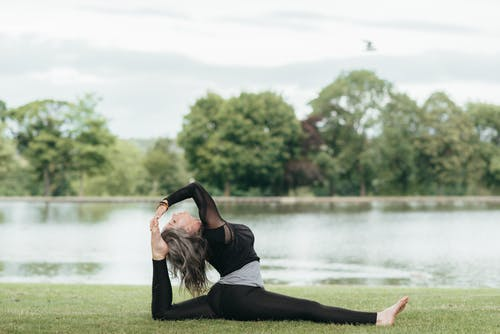 Side view of young flexible female in sports clothes sitting in Front Splits pose with raised leg on grass shore
