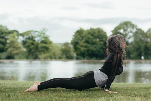 Woman performing High Cobra pose on grass shore