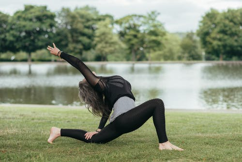 Unrecognizable woman performing Crescent Lunge pose on river coast