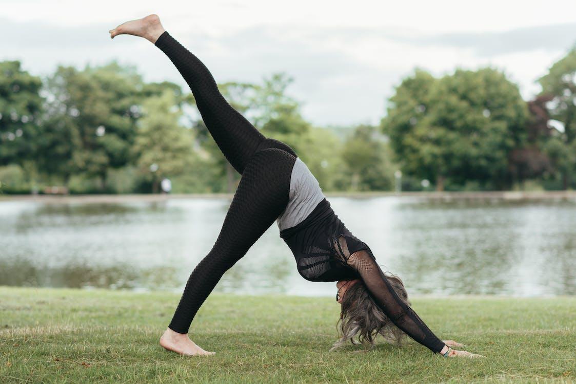 Side view of anonymous flexible female in sportswear standing in Eka Pada Adho Mukha Svanasana pose while practicing yoga on river coast