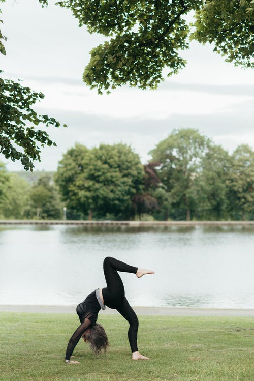 Side view of anonymous flexible lady in sports clothes standing in Eka Pada Urdhva Dhanurasana pose while practicing yoga against pond and trees
