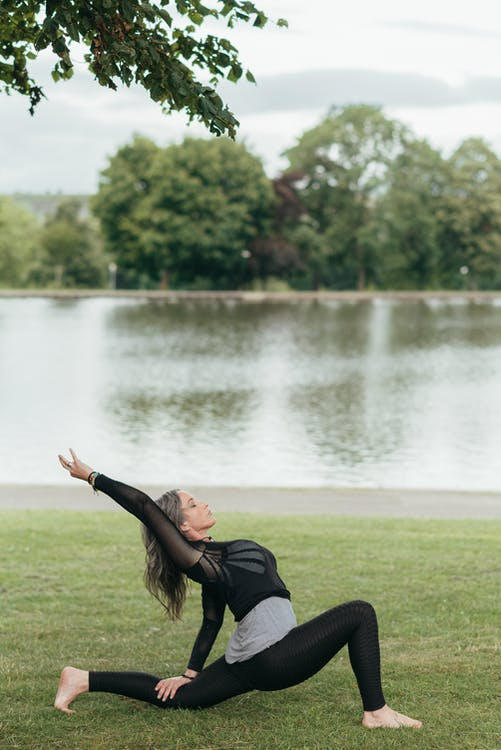 Flexible woman performing Crescent Lunge pose on grass shore