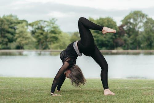 Side view of anonymous flexible female standing in Eka Pada Urdhva Dhanurasana pose while practicing yoga on river shore
