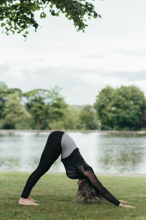 Unrecognizable woman showing Downward Facing Dog pose on grass shore