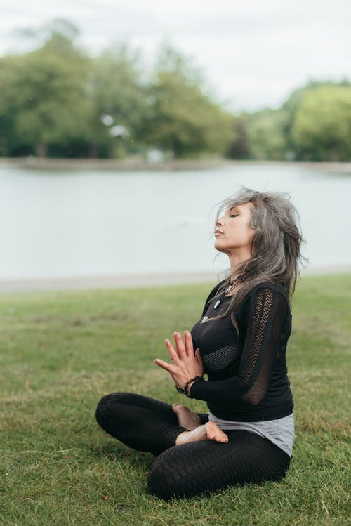 Mindful woman meditating with praying hands in Lotus pose