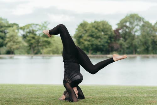 Young barefoot female in sports clothes standing on head with raised legs while practicing yoga on river shore