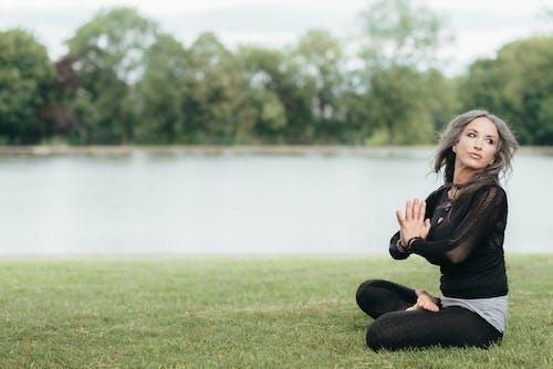 Verträumte Frau, Die In Lotushaltung Mit Betenden Händen Sitzt