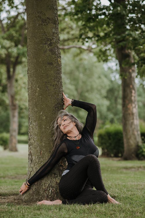 Young contemplative barefoot female in sports clothes sitting with crossed legs and raised arm on lawn near tree while practicing yoga and looking away