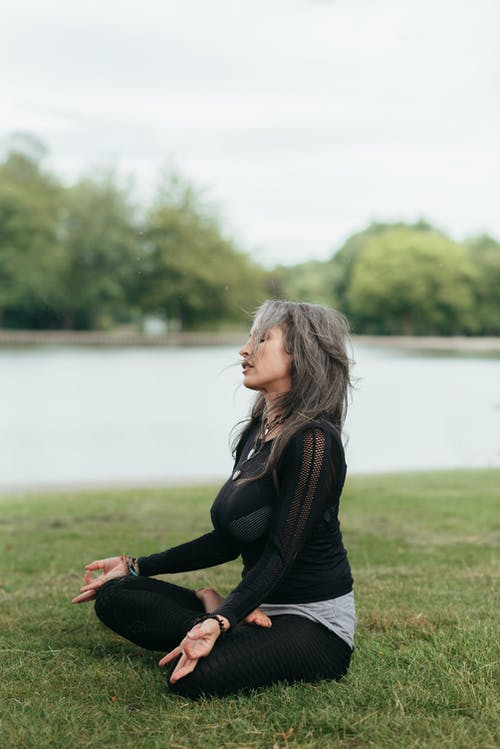 Concentrated woman meditating in Lotus pose on river shore