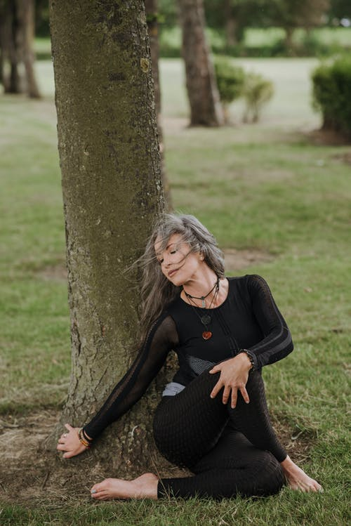 Mindful woman performing Seated Twist pose near tree