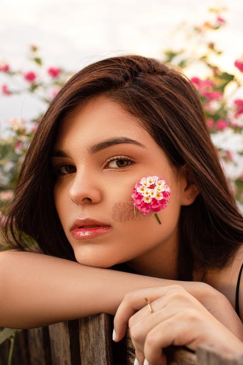 Sensual woman with flower on cheek