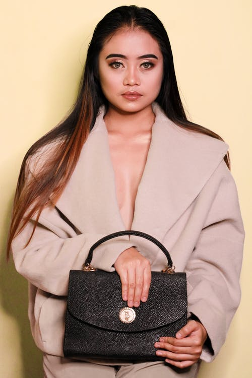 Woman in stylish clothes with black purse in studio