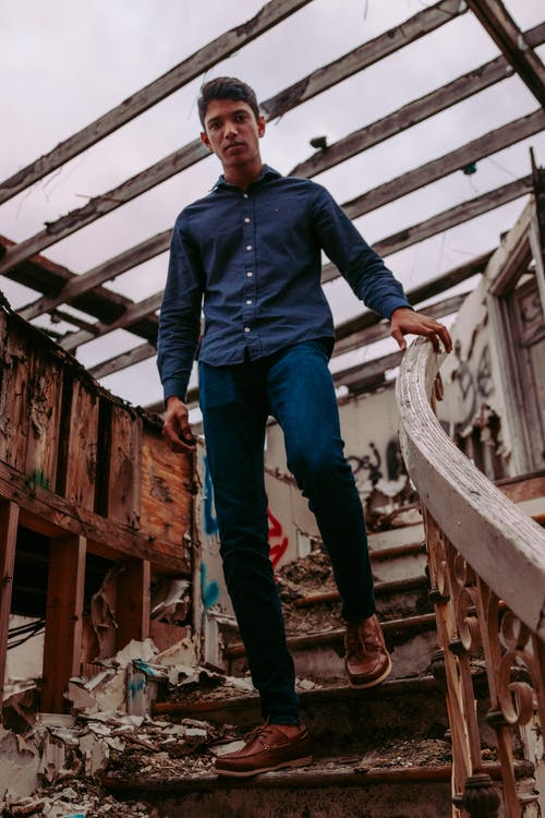 Man in Blue Dress Shirt and Blue Denim Jeans Standing on Brown Wooden Bridge
