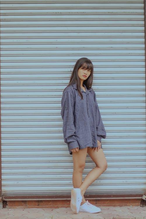 Woman in long shirt standing near wall