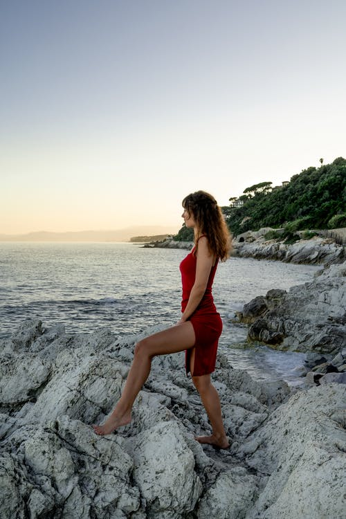 Woman in Red Tank Top and Red Shorts Standing on Rocky Shore