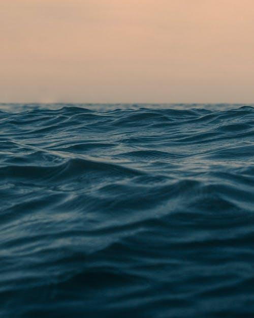 Wavy ocean with horizon under sky at sunset