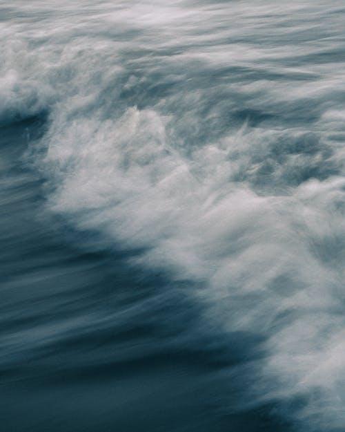 Sea with splashing foamy waves in evening