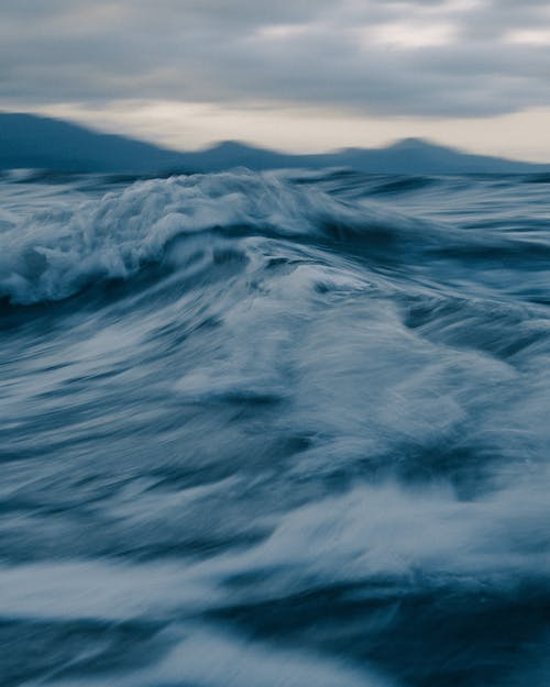 Stormy sea with fast foamy waves at sunset