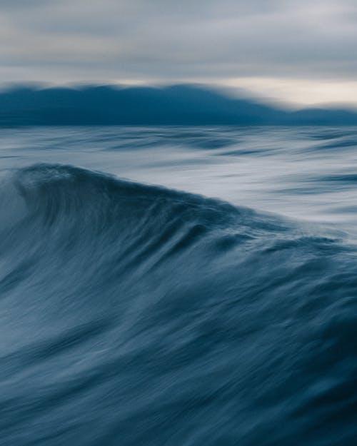 Rapid wave on stormy sea behind ridge in twilight
