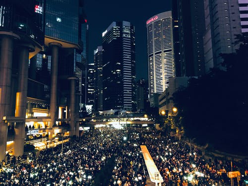 Illuminated buildings on crowded city street at night