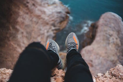 Anonymous traveler admiring sea from rough cliff