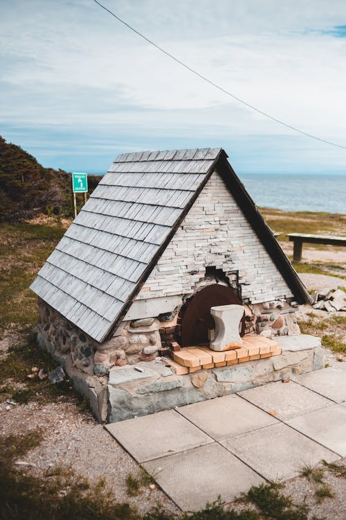 From above of small old pizza oven on dry terrain near ocean under cloudy sky