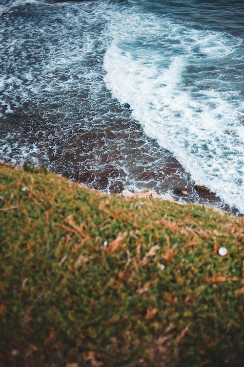 Grass mountain near stormy ocean with foam