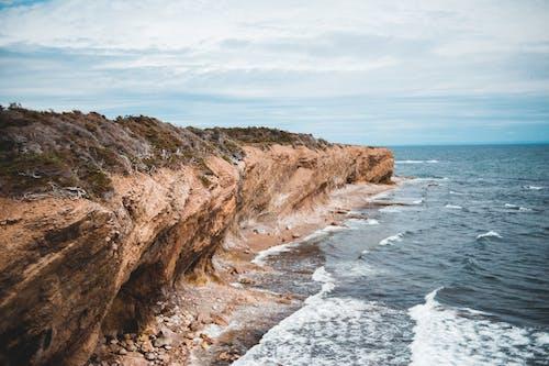 Rough cliff near wavy sea under sky