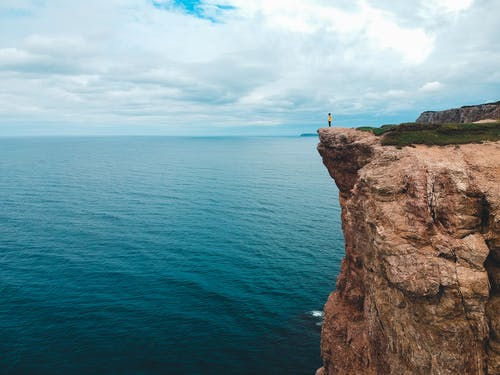 Person standing on cliff over ocean