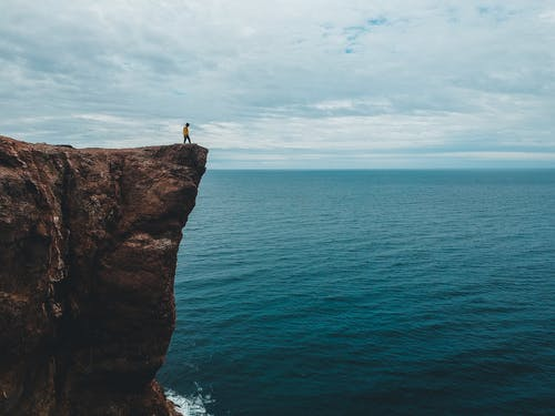 Grey overcast sky covered with clouds above tourist standing on edge of tall majestic dark brown cliff over wavy blue endless ocean