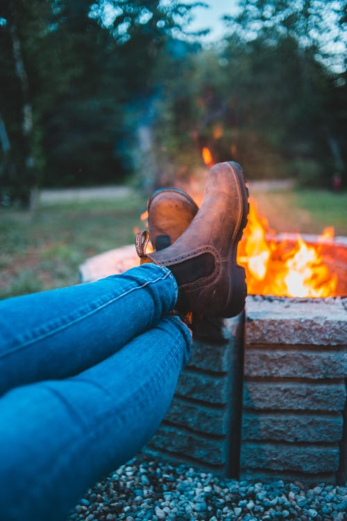 Unrecognizable tourist in jeans and boots chilling with legs crossed by bright bonfire in big fire bowl in forest on blurred background