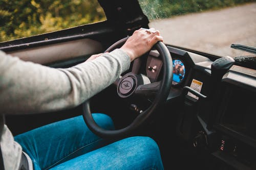 Faceless driver in grey sweater and jeans using big black round spinning wheel while driving automobile in countryside