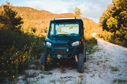 Aged all terrain vehicle near shabby pathway between bright trees growing on mount under cloudy sky