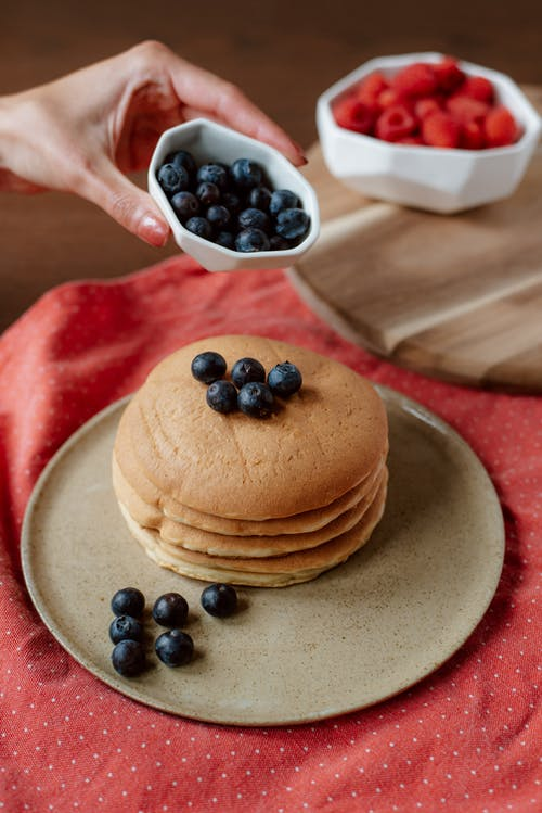 Crop woman decorating delicious pancakes with fresh blueberries