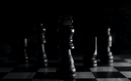 Black Chess Piece on a Chess Board