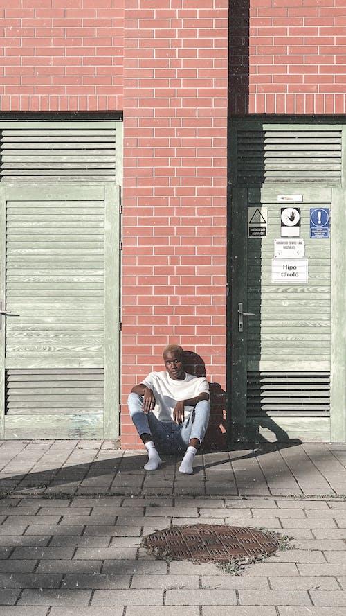 A Man Sitting on the Street Sidewalk